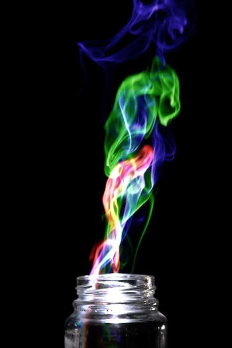 Multi Colored smoke coming from a glass jar, on black background. Achieved by the 'Harris effect' creative photography projects.