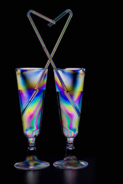 Two cocktail glasses filled with a multicolored photoelasticity effect on black background
