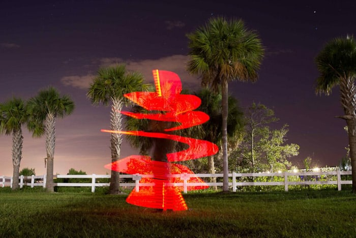 A palm tree at night, with red spiral light painting wrapped around it