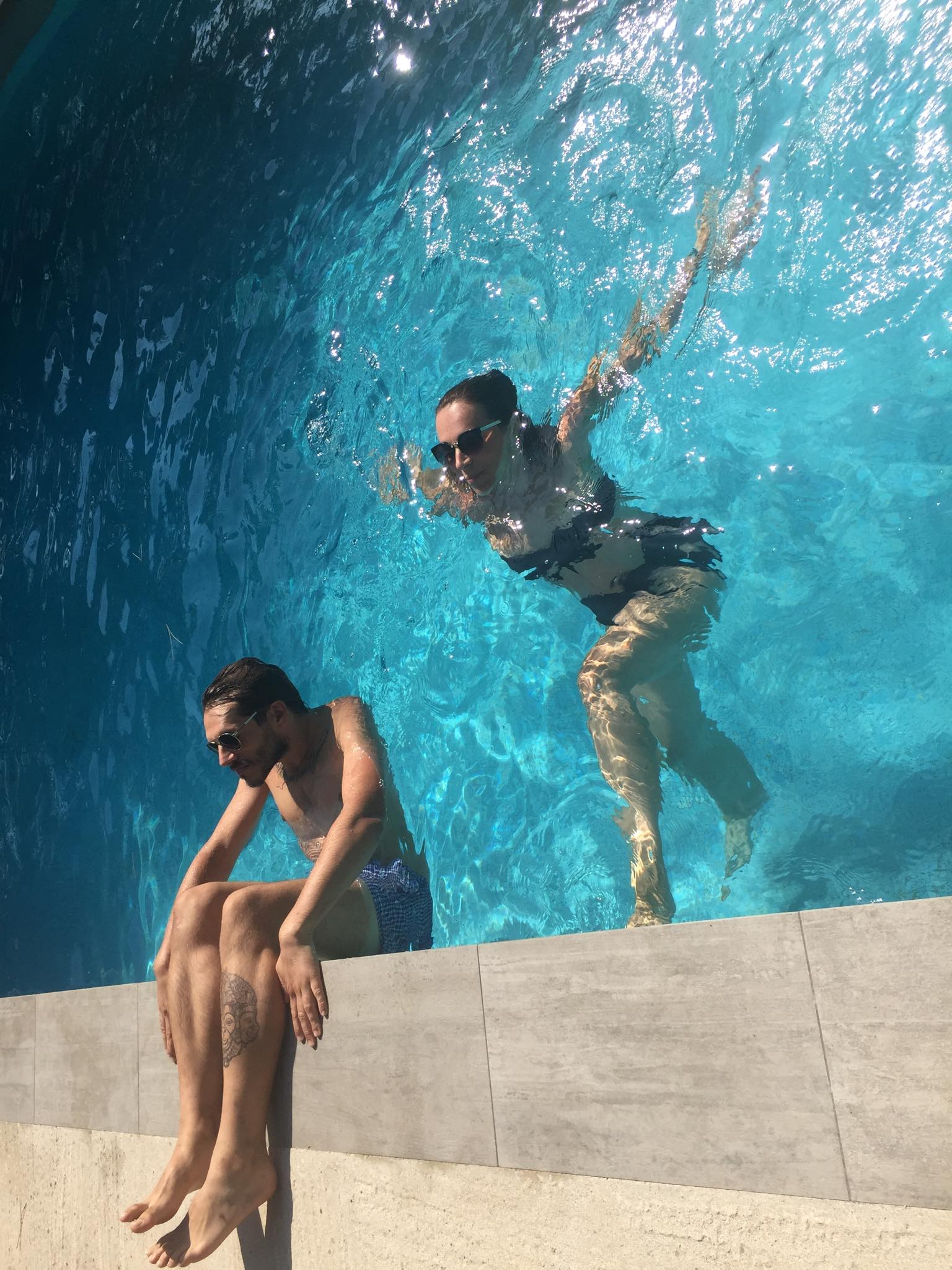 Forced perspective shot of two people in a swimming pool