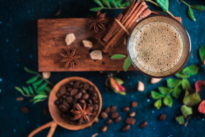 An overhead still live of coffee cups, coffee beans, cinnamon sticks and foliage on a wooden board