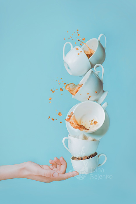 Fun coffee photography shot of six falling cups balanced on the tip of someones finger