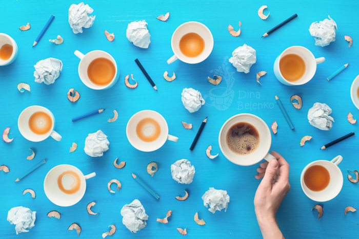 Overhead still life of nine coffee cups, balls of paper and pencils on sky blue background
