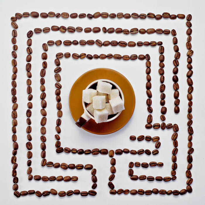 Overhead shot of a maze of coffee beans with a cup of sugar cubes in the centre