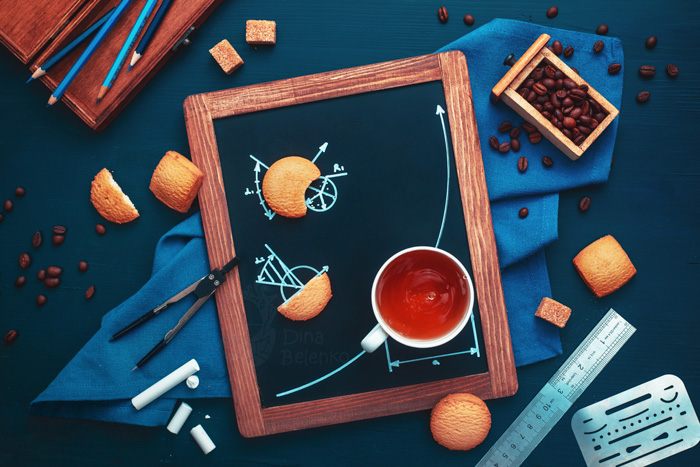 Overhead still life using coffee cups, biscuits, chalkboard, pencils and coffee beans to tell a story about a high school kid doing their geometry homework