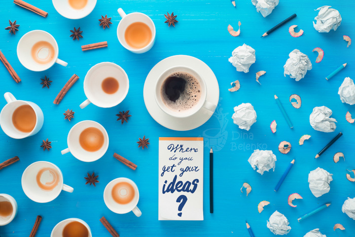 Overhead still life of coffee cups, cinnamon sticks, balls of paper and pencils with a notepad with the words 'where do you get your ideas' on sky blue background
