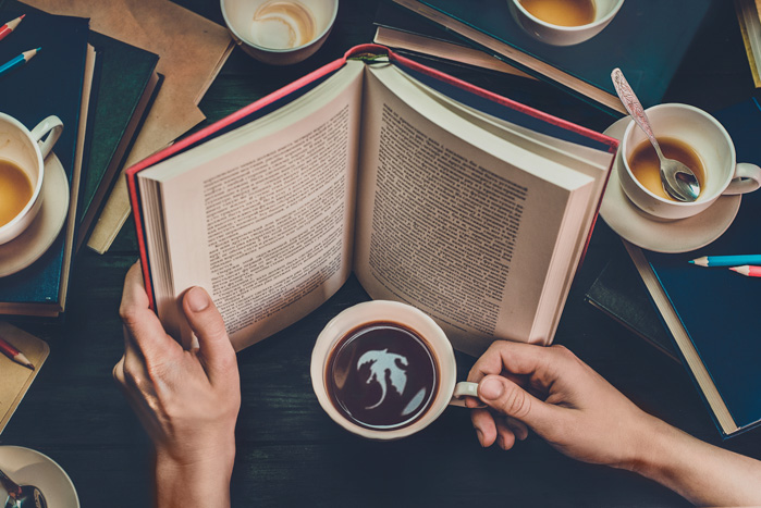 Conceptual still life shot of a person reading a fantasy book and seeing a dragon in a coffee cup reflection.