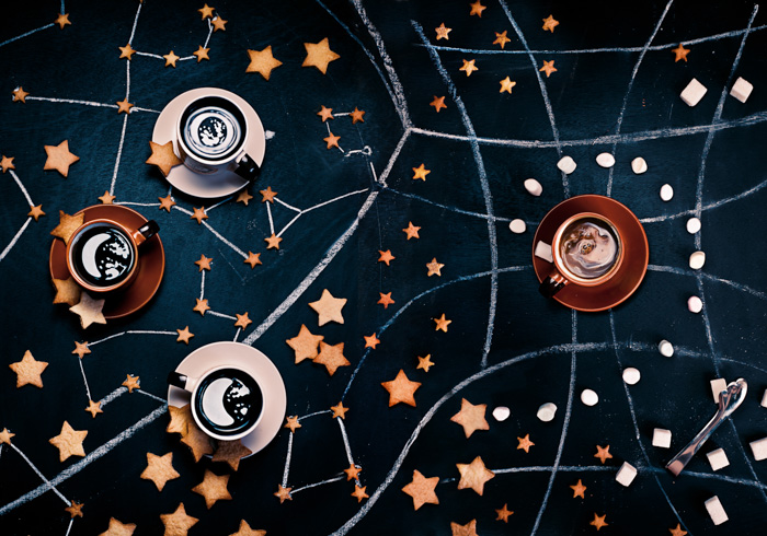 Overhead still life of coffee cups, biscuits and chalk lines arranged like a star map