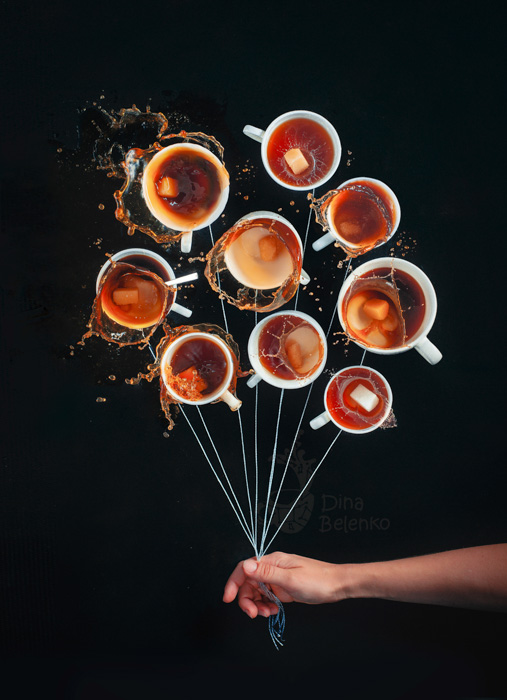 A playful food photography shot of a person holding strings to nine coffee cups as if they were holding a bunch of balloons