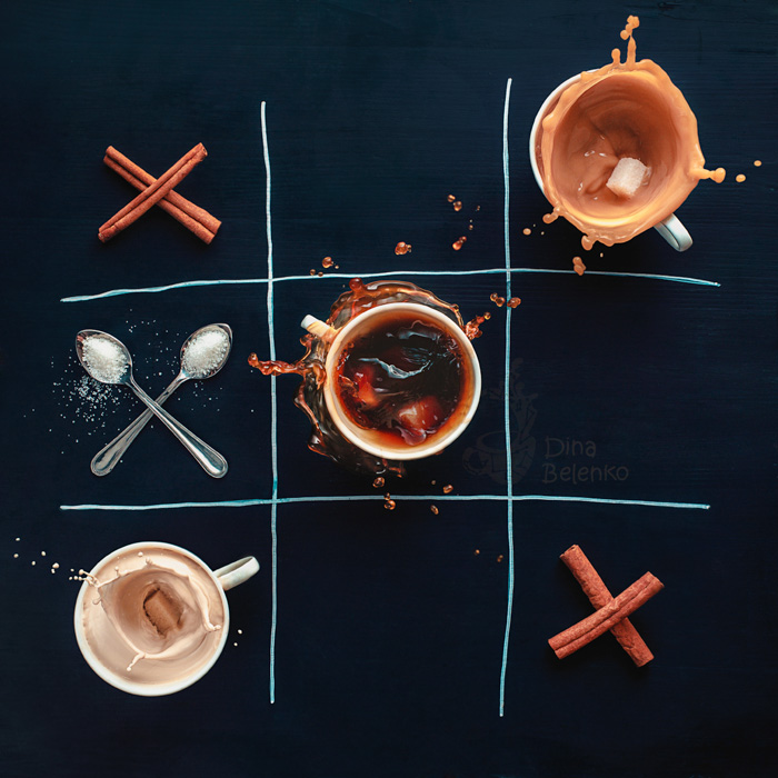 An overhead creative coffee photography shot of the game tic tac toe created with coffee cups, cinnamon sticks and spoons
