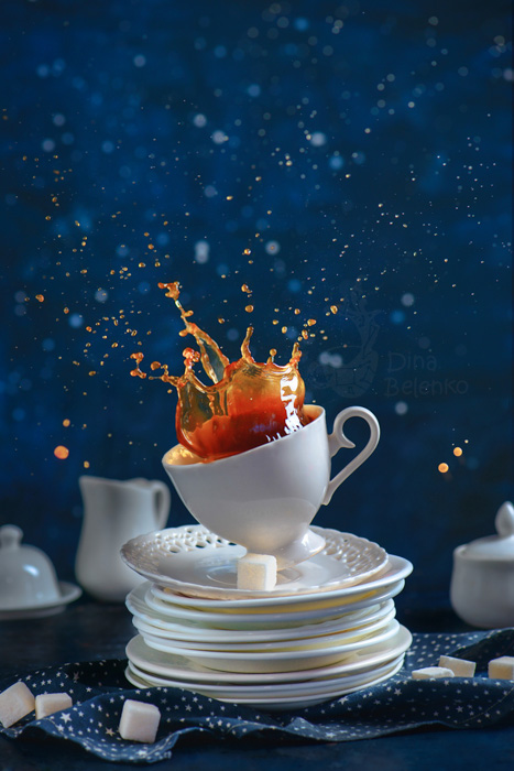 A playful food photography shot of a coffee cup with splashes balancing on a pile of white saucers against a blue background