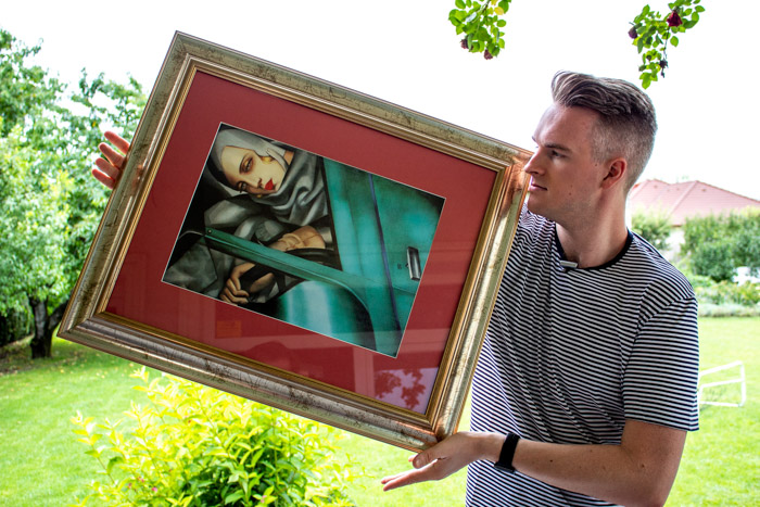 A man holding a framed painting outdoors