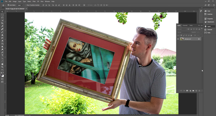 Screenshot of Photoshop editing a picture of a man holding a framed painting - droste effect step one