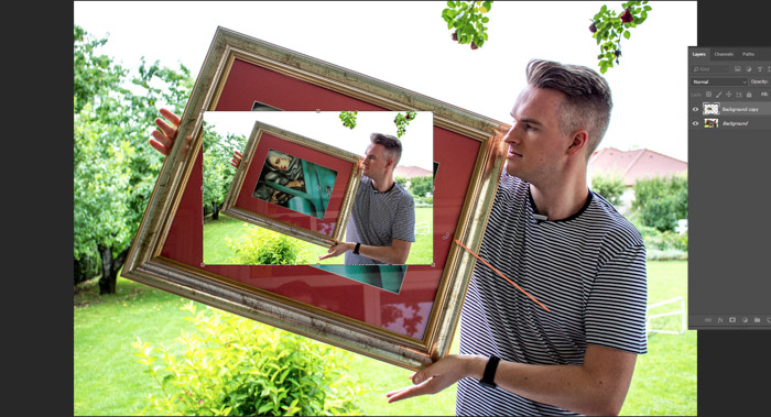Screenshot of Photoshop editing a photo of a man holding a framed painting