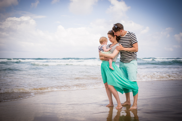 Lifestyle shot of a couple with a small baby standing on the beach - composition for family portraits