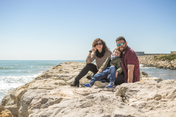 Sweet family portrait photography of a man, woman and child on the beach - family photo ideas