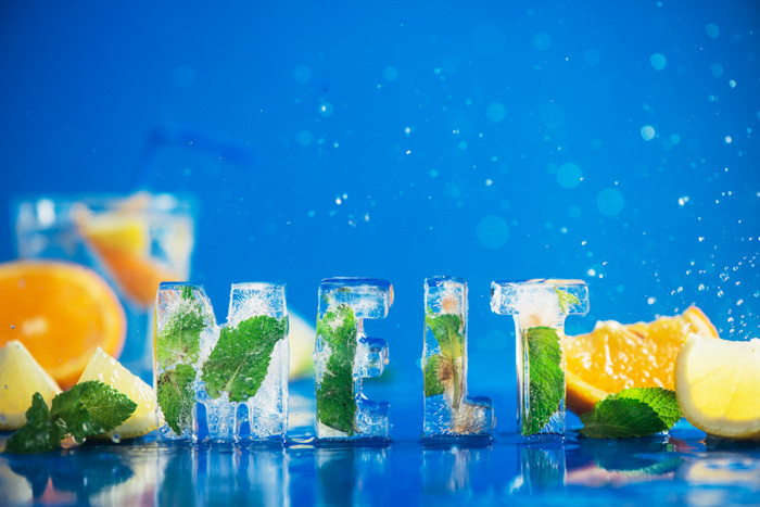Ice cube lettering with frozen mint leaves, lemon slices and oranges on a blue background with water splashes. Text says Melt. Water drop bokeh. Copy space.