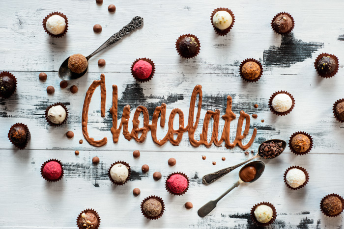 The word chocolate made from food typography glazing with chocolates, candies and tea spoons on a white wooden background.