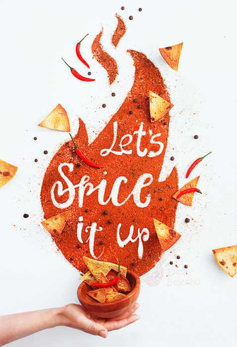 A hand holding a bowl of chips with the typography message 'lets spice it up' with nachos and spices