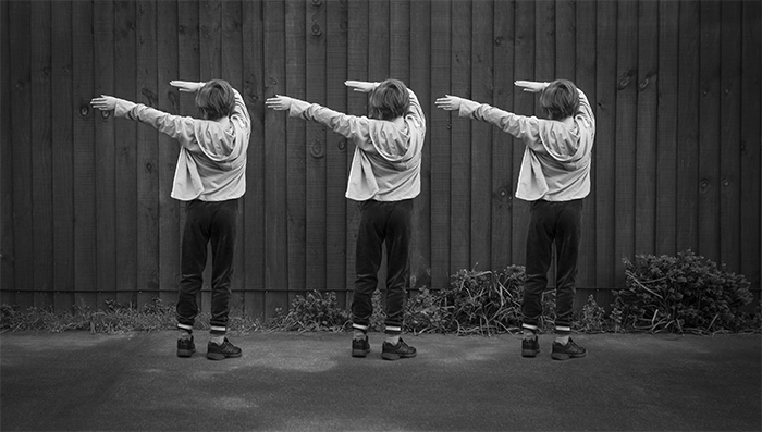 A black and white multiplicity photography example of three of the same little girl dancing outdoors