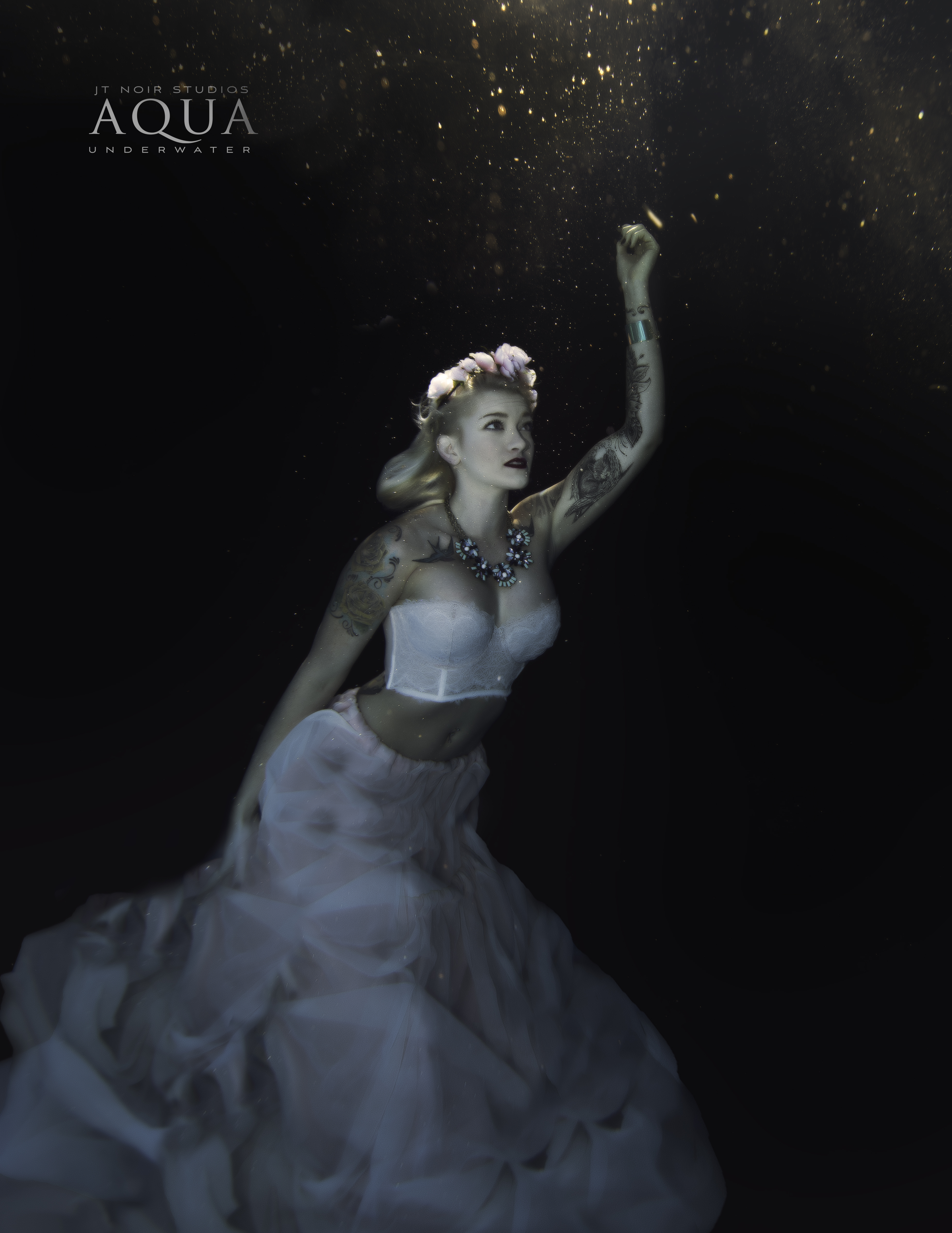 A stunning advertising photo of a woman with flowing white dress underwater