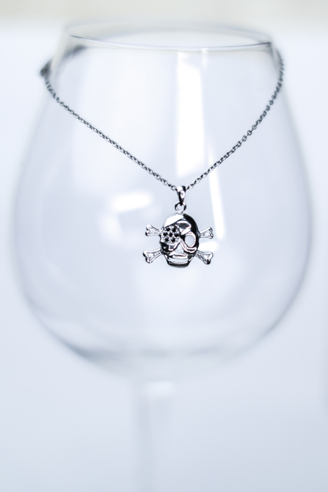A jewelry photography close up of a cool silver jolly roger necklace displayed on a wine glass