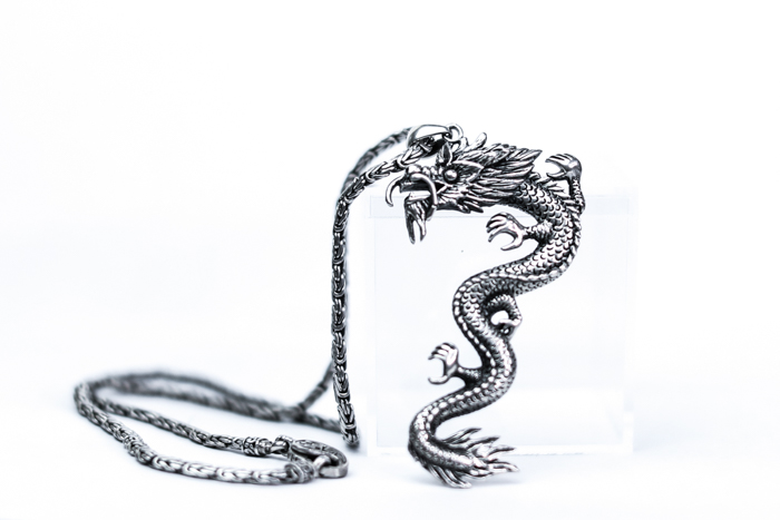 A jewelry photography close up of a cool silver dragon necklace on white background
