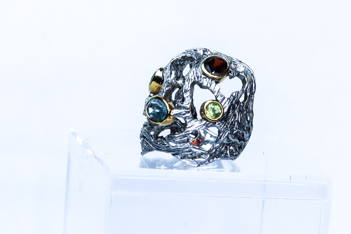 A jewelry photography close up of a silver and colored jewelled ring with a white background