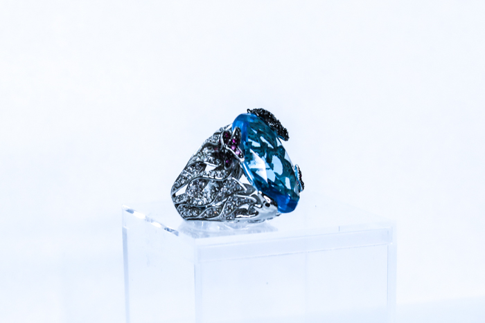 A jewelry photography close up of a turquoise jeweled ring with a white background