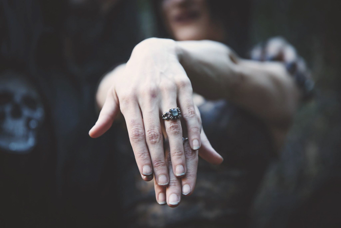 Portrait of a female jewelry photography model with her hands clasped close to the camera