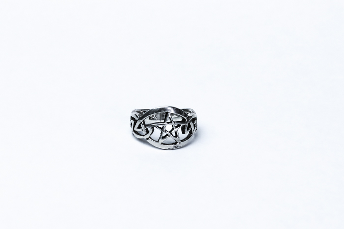 A jewelry photography close up of a silver ring with a white background