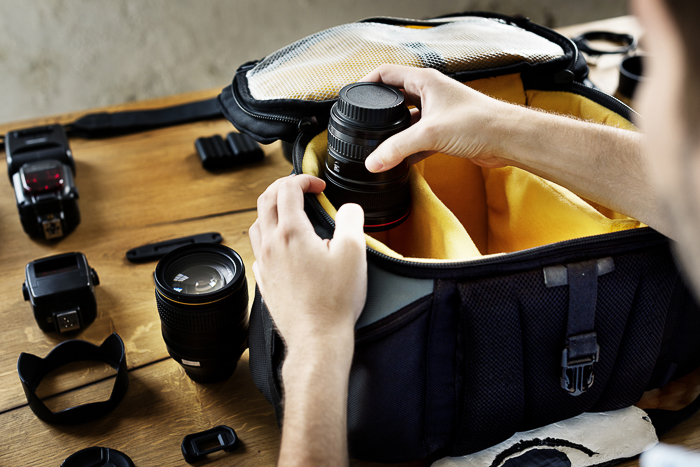 A person organising their travel photography camera bag