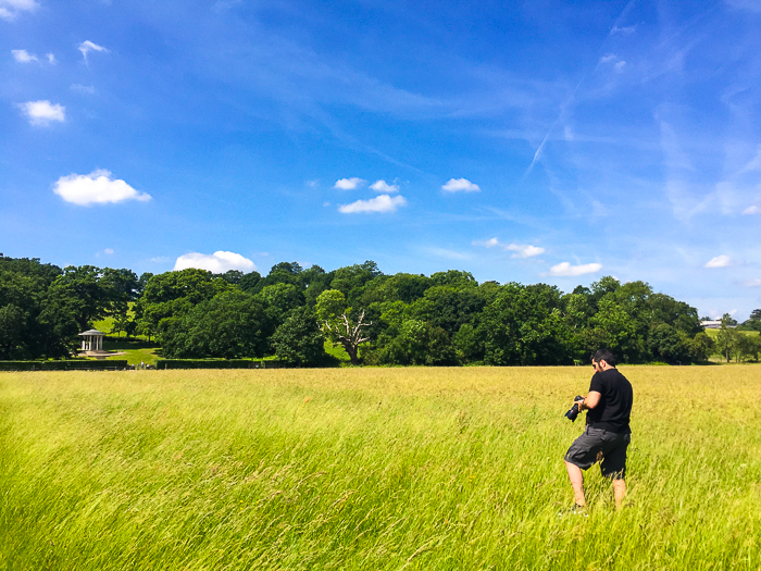 A photographer checking his camera settings in a grassy landscape on a clear day with blue skies