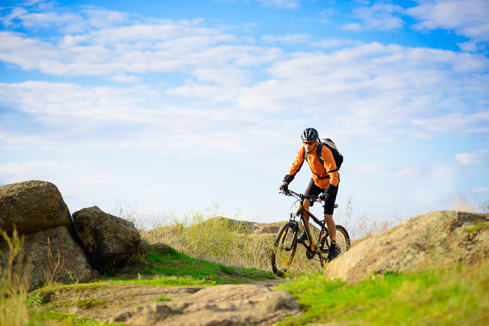 A mountain biker riding through a grassy countryside area on a bright day
