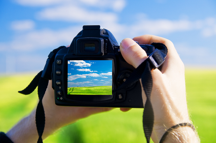 Close up of a person checking their DSLR camera settings for landscape photography