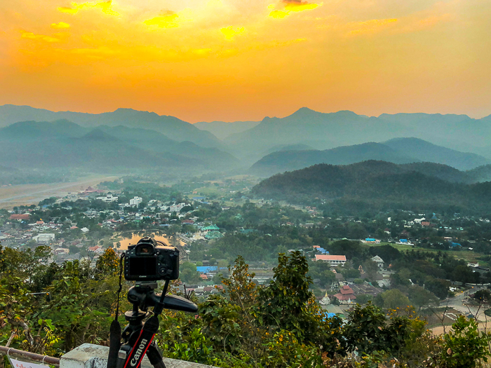 A Canon DSLR camera on a tripod, pointed at a beautiful landscape at sunset