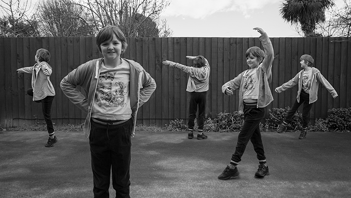 A black and white, wide angle multiplicity photography example of five of the same little girl dancing outdoors