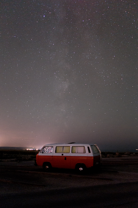 Image of a red camper van parked under an impressive starry sky