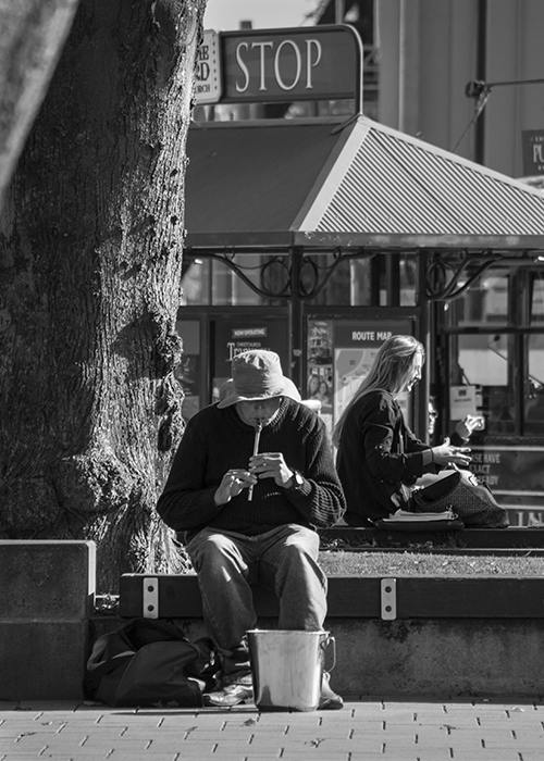Black and white street portrait of a man playing a flute outdoors on a bright sunny day - street photography lighting