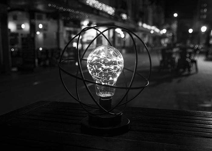 A black and white street shot of a lightbulb sculpture on a wooden table at night