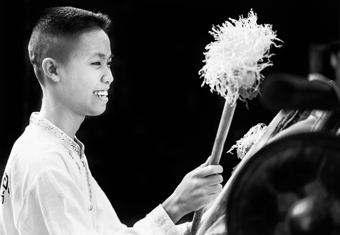 Portrait of a teenage boy playing a large drum during the annual flower parade in Chaing Mai, Thailand. Black background photography.