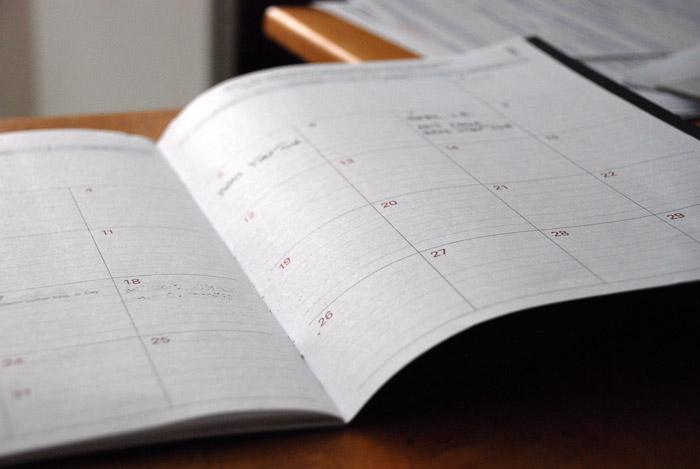 Close up shot of a calendar book regarding a boudoir shoot on a table
