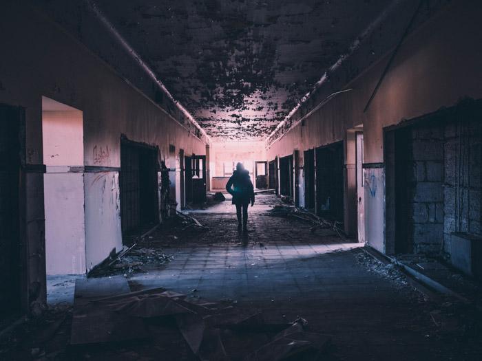 An urban explorer walking through the corridor of an abandoned building