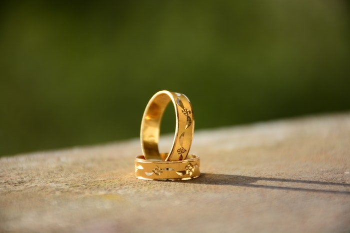 two gold rings on a table