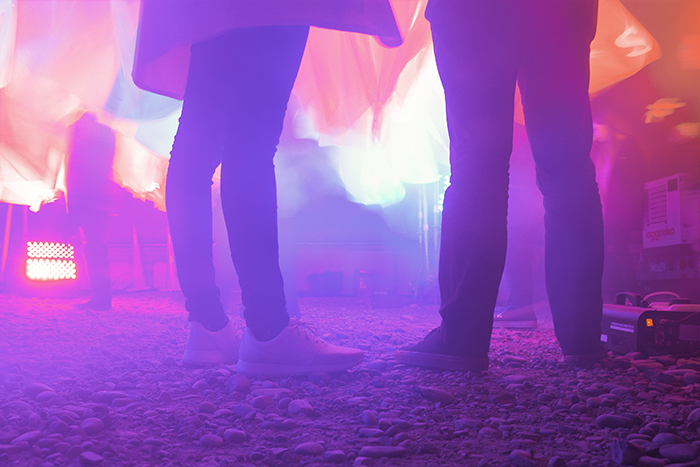 Pink and purple artificially lit photo of peoples legs while standing at an event - using color in photography