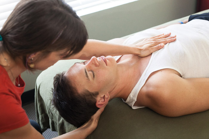 A business portrait of a woman giving a massage to a man lying on a table - commercial photography example