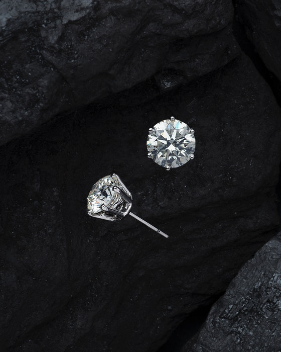 two diamond earrings on a black background