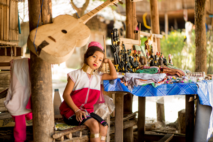 An environmental portrait photography shot of a young Kayan girl beside the table of trinkets she sells outside the family home.