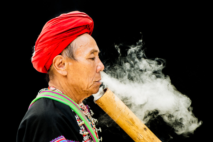 An environmental portrait photography shot of a Lahu man smoking against a black background