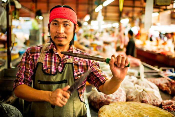An environmental portrait photo of a market butcher in Thailand